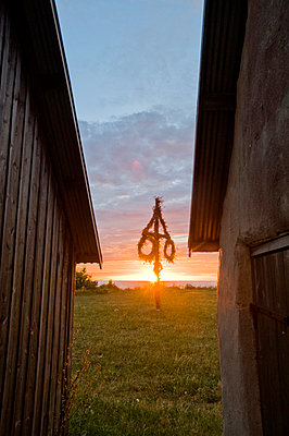 A maypole between two houses, Sweden. - p5755337f by Fredrik Schlyter