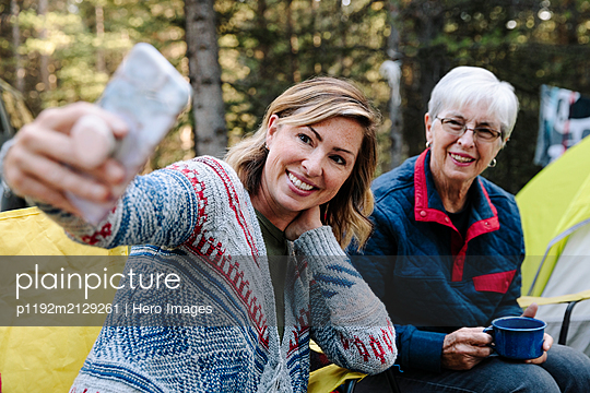 Happy senior mother and daughter taking selfie at campsite - p1192m2129261 by Hero Images