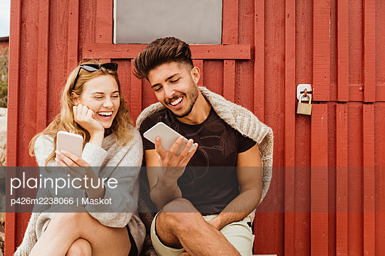 Friends laughing while using mobile phone against cottage - p426m2238066 by Maskot