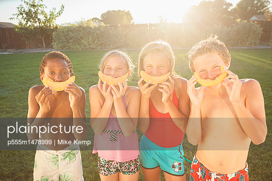 Children eating cantaloupe - p555m1478999 by Mike Kemp
