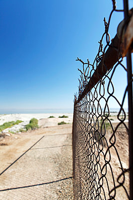 Wire fence on the beach - p1105m2063401 by Virginie Plauchut