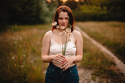 Young woman holding bunch of dandelion flowers standing on meadow - p1166m2153309 by Cavan Images