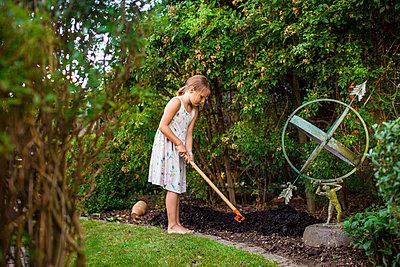 Full length of girl spreading fertilizer in backyard - p1264m1089084f by Astrakan