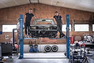 Two young men alongside a car on a hydraulic ramp - p1437m2253431 by Achim Bunz