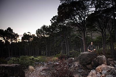 Hiker sits on boulder at twilight - p1640m2261049 by Holly & John