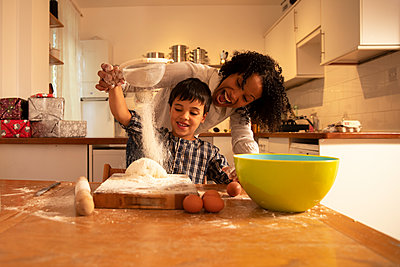 Cheerful mother screaming while mixing ingredients with son on table in kitchen - p300m2243277 by Pete Muller