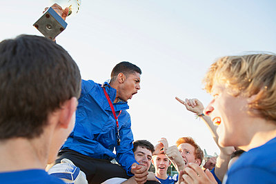 Teenage soccer team lifting up coach with trophy. - p328m840869f by Hero Images