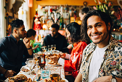 Portrait of smiling young man sitting with multi-ethnic friends enjoying dinner party at restaurant - p426m2046333 by Maskot