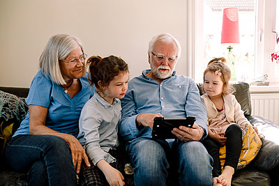 Grandparents sitting with grandchildren while using digital tablet in living room at home - p426m2118595 by Maskot