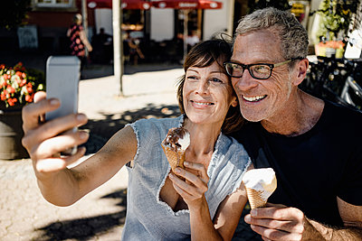 Mature couple takes a selfie while eating ice cream - p586m2109200 by Kniel Synnatzschke
