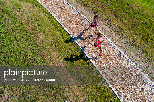 Aerial view of female joggers on woodchip trail - p300m2004677 von Stefan Schurr