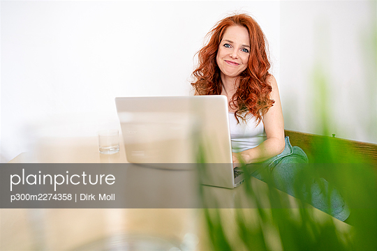 Portrait of smiling redhead woman sitting with laptop at table against white wall in room - p300m2274358 by Dirk Moll