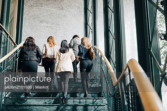 Low angle view of multi-ethnic female entrepreneurs moving up on staircase in office - p426m2101935 by Maskot