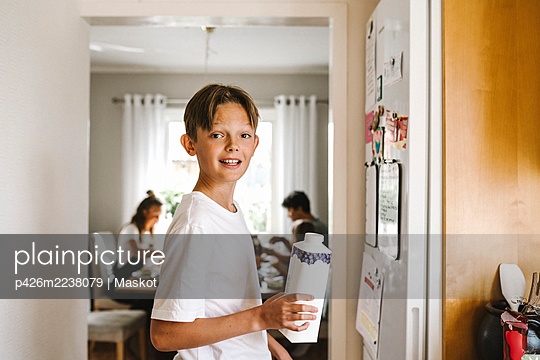 Boy with juice pack standing in kitchen - p426m2238079 by Maskot