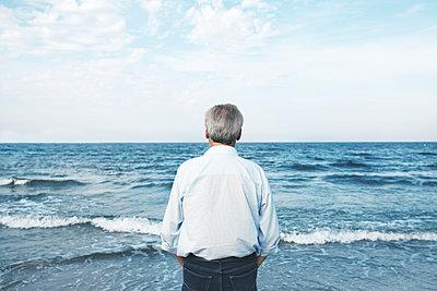 Mann blickt aufs Meer hinaus - p1006m1425235 von Danel