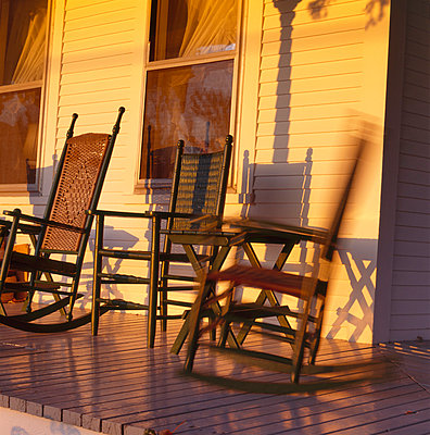Two wooden chairs on a wooden veranda bathed in yellow light - p1072m829000 by George Robinson