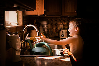 A Young Boy Curious With Water From The Kitchen Sink - p1166m2094733 by Cavan Images