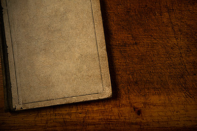 Old book with blank cover resting on old wooden desk top - p1427m2283091 by Tom Grill