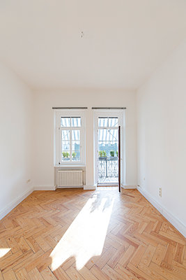 Empty room with herringbone parquet  and opened balcony door - p300m1449438 by Christina Falkenberg