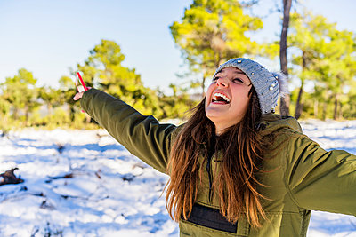 Carefree woman laughing while standing with arms outstretched in forest during winter - p300m2250928 by Javier De La Torre Sebastian