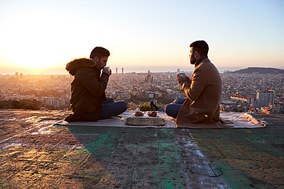 Gay couple having breakfast while sitting on observation point, Bunkers del Carmel, Barcelona, Spain - p300m2257330 by Veam