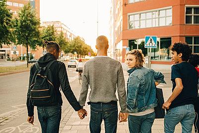 Rear view of male friends walking side by side on street in city - p426m2075089 by Maskot