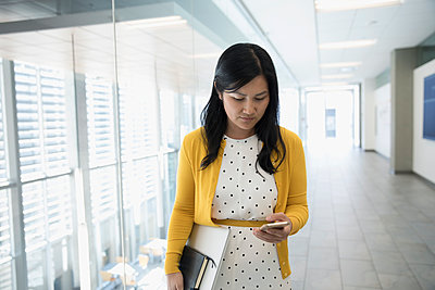 Asian businesswoman texting with cell phone in office corridor - p1192m1493337 by Hero Images