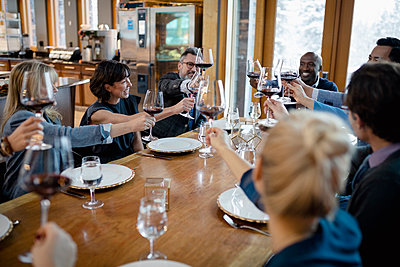 Business people toasting red wine glasses at restaurant table - p1192m2047257 by Hero Images