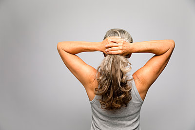 Rear view portrait woman with hands in long, gray hair - p1192m2124409 by Hero Images