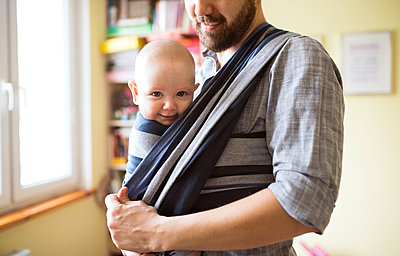 Father with baby son in sling at home - p300m1417101 by HalfPoint