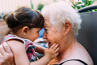 Grandmother face to face with her  granddaughter on terrace - p300m2029073 by Gemma Ferrando
