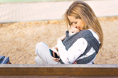 Happy mother resting with baby boy on a park bench - p300m2155977 by Eloisa Ramos