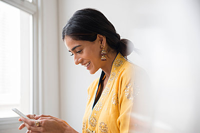 Indian woman texting with cell phone - p555m1305065 by JGI/Jamie Grill