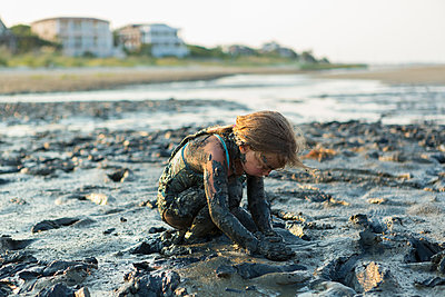 Caucasian girl covered in mud playing on beach - p555m1522789 by Marc Romanelli