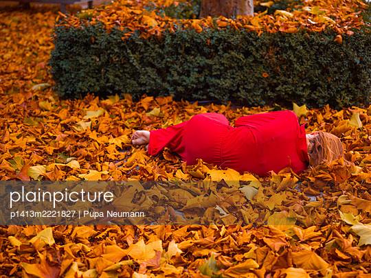 Woman in red dress lying on dried autumn leaves - p1413m2221827 by Pupa Neumann
