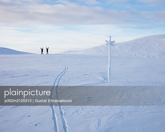 Men holding ski poles aloft on snow - p352m2120313 by Gustaf Emanuelsson