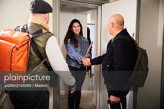 Smiling woman handshaking with senior man while standing with friend at doorway - p426m2165550 by Maskot