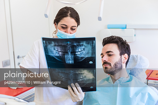 Female dentist and male patient looking at dental x-ray