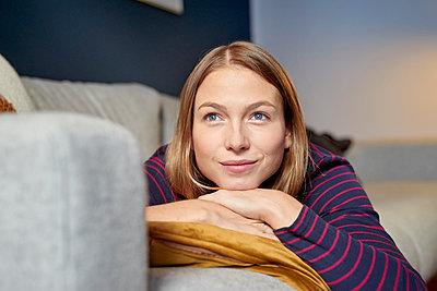 Junge Frau entspannt sich in ihrer Wohnung - p1124m1589197 von Willing-Holtz