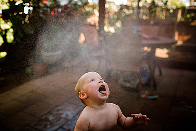 One Year Old Boy Catching Water with Tongue in San Diego - p1166m2216883 by Cavan Images