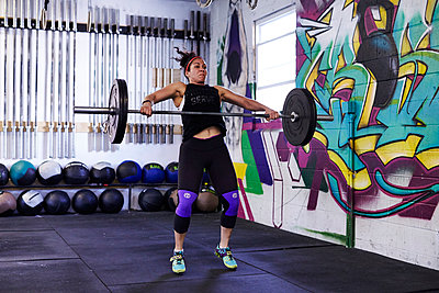 A female athlete trains in a crossfit gym.  - p343m1184147 by Josh Campbell