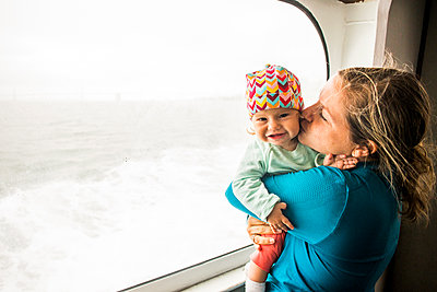Caucasian mother kissing baby daughter at window - p555m1411237 by Adam Hester