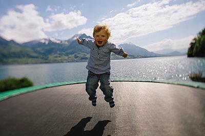 Kleiner Junge auf einem Trampolin, Vierwaldstättersee - p819m1066364 von Kniel Mess