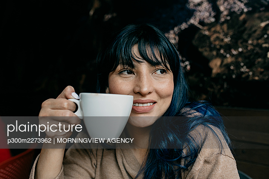 Smiling woman day dreaming while holding coffee cup - p300m2273962 by MORNINGVIEW AGENCY