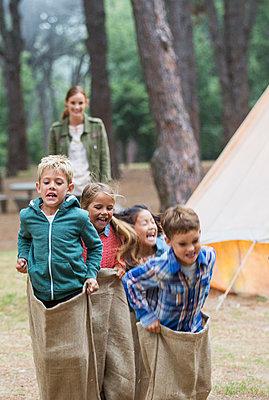 Children having sack race at campsite - p1023m1146446 by Paul Bradbury