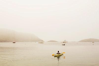 Woman kayaking in sea against clear sky - p1166m1105559f by Cavan Images