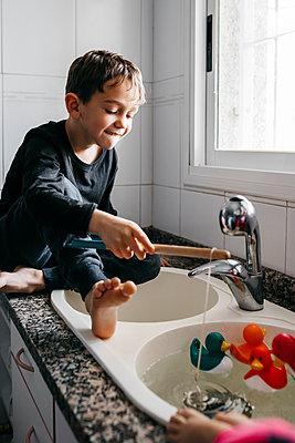 Boy fishing rubber ducks in kitchen sink - p300m2189091 by Josep Rovirosa