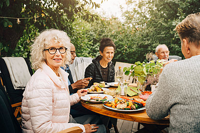 Portrait of smiling senior woman sitting with friends at dining table during dinner party - p426m2195135 by Maskot