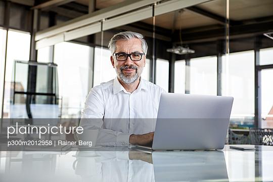Portrait of confident businessman with laptop at desk in office - p300m2012958 von Rainer Berg