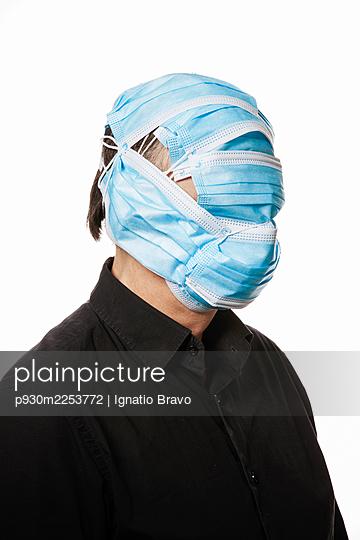 Gesicht eines Mannes bedeckt mit OP-Masken - p930m2253772 von Ignatio Bravo